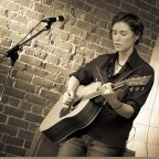 Credit: Erin Kelly - Catherine playing acoustic in front of brick wall