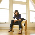 Credit: Rob Waymen - Catherine sitting on modern wooden chair against arched windows
