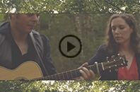 Catherine MacLellan and Chris Gauthier playing acoustic guitar on country road